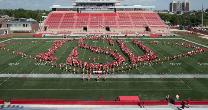 students form the letters I.S.U. on the playing field
