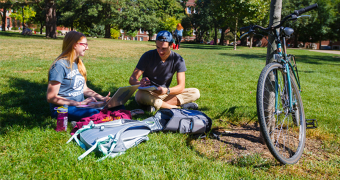 Male and female students studying on the quad with a bike nearby.